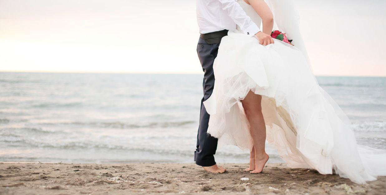 """alt=""""Novios celebrando boda en la playa"""" />"""